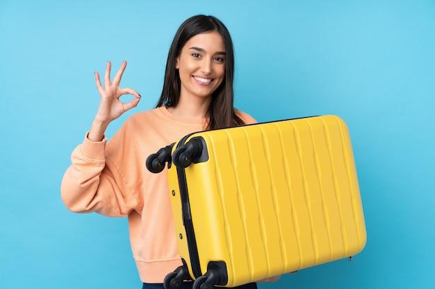 Jovem morena sobre parede azul isolada em férias com mala de viagem e fazendo sinal ok