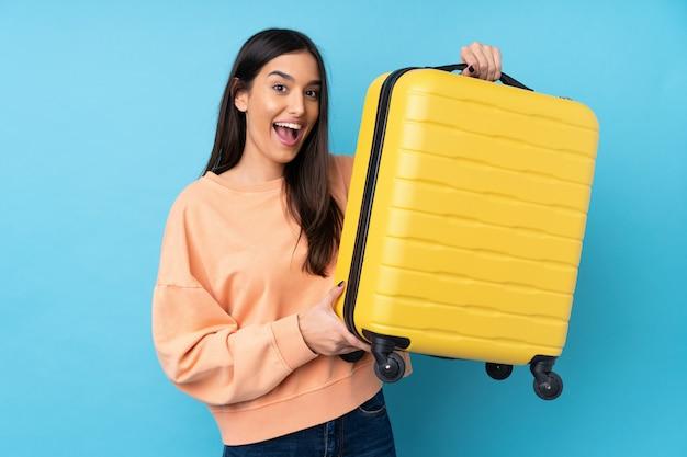 Jovem morena sobre parede azul isolada em férias com mala de viagem