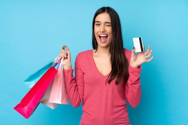 Jovem morena sobre parede azul isolada segurando sacolas de compras e um cartão de crédito