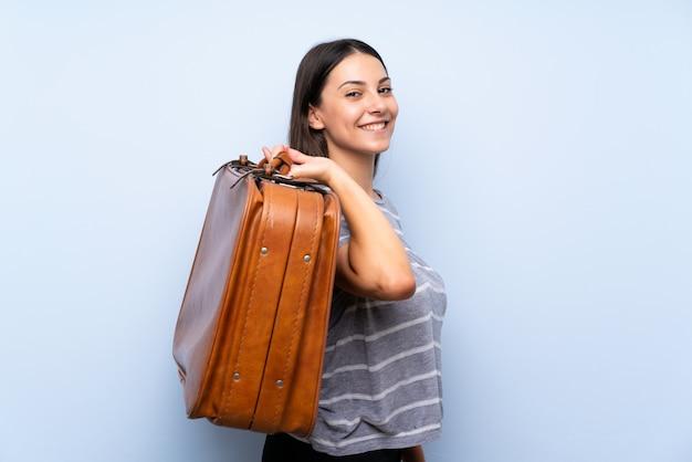 Jovem morena sobre parede azul isolada, segurando uma mala vintage