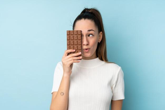 Jovem morena sobre parede azul isolada, tomando uma tablete de chocolate e surpreendeu