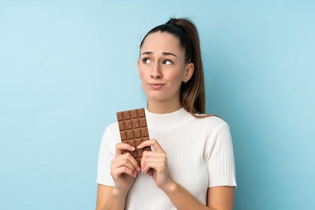 Jovem morena sobre parede azul isolada, tomando uma tablete de chocolate e tendo dúvidas