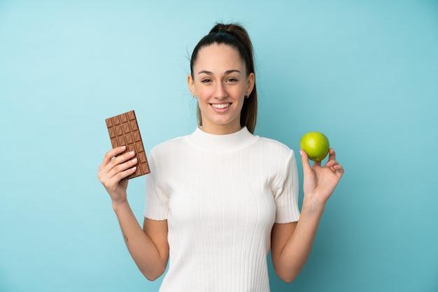 Jovem morena sobre parede azul isolada, tomando uma tablete de chocolate em uma mão e uma maçã na outra