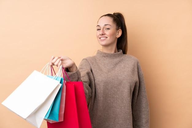 Jovem morena sobre parede isolada segurando sacolas de compras e dando a alguém