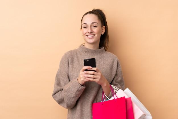 Jovem morena sobre parede isolada segurando sacolas de compras e escrever uma mensagem com o celular para um amigo