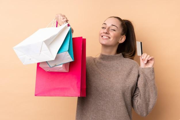 Jovem morena sobre parede isolada segurando sacolas de compras e um cartão de crédito