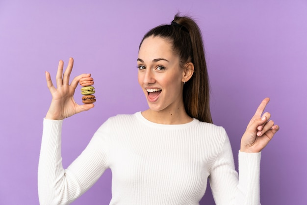 Jovem morena sobre parede roxa isolada segurando macarons franceses coloridos e apontando uma ótima idéia