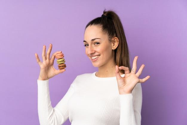 Jovem morena sobre parede roxa isolada segurando macarons franceses coloridos e mostrando sinal de ok com os dedos