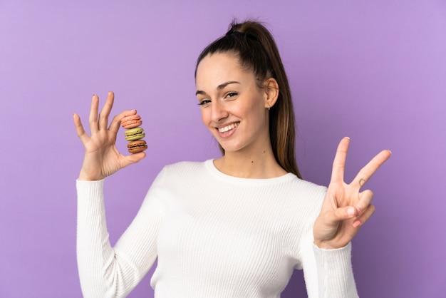 Jovem morena sobre parede roxa isolada segurando macarons franceses coloridos e mostrando sinal de vitória