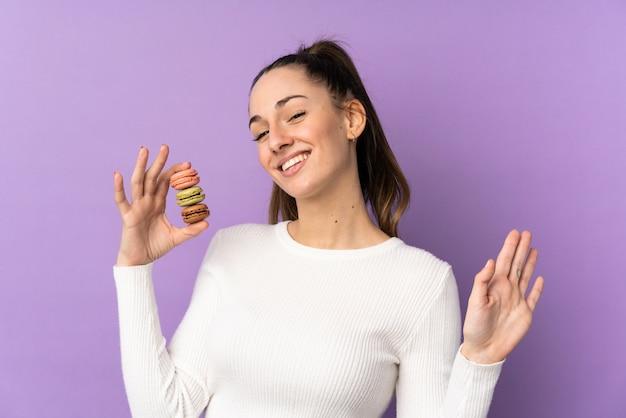 Jovem morena sobre parede roxa isolada segurando macarons franceses coloridos e saudação