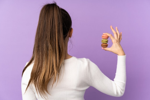 Jovem morena sobre parede roxa isolada segurando macarons franceses coloridos em posição traseira
