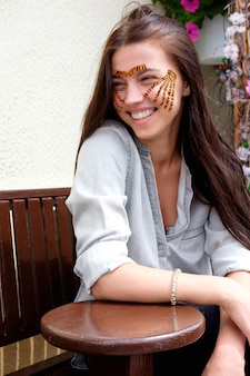 Jovem morena sorridente atraente com fitas coloridas de tigre após gravar o procedimento de rosto no salão de beleza, sentado na rua