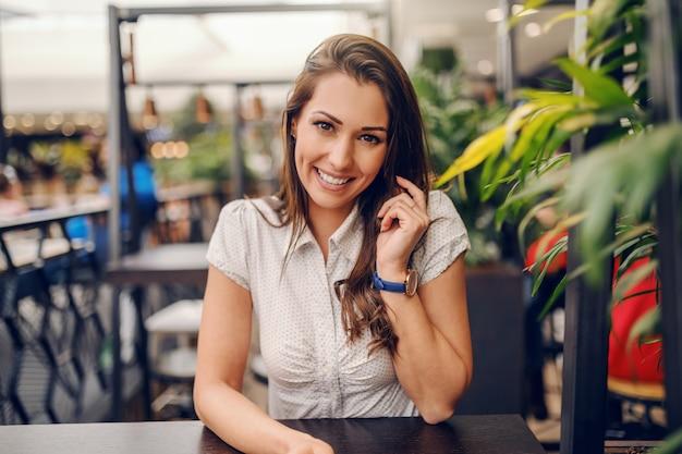 Jovem morena sorridente caucasiana sentado no café e usando telefone inteligente para chamada.