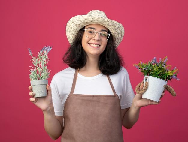 Jovem morena sorridente com óculos e uniforme, usando chapéu de jardinagem, segurando vasos de flores isolados na parede rosa com espaço de cópia