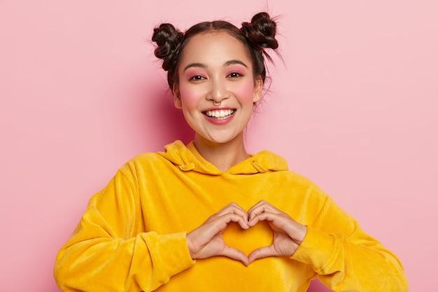 Jovem morena sorridente confessa sentimentos verdadeiros, faz gesto de coração, vestida com capuz amarelo, mostra gesto de coração