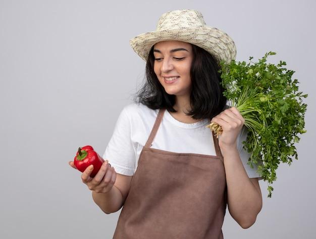 Jovem morena sorridente jardineira de uniforme, usando chapéu de jardinagem, segurando coentro e olhando para pimenta vermelha isolada na parede branca