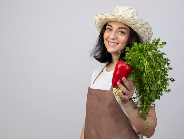 Jovem morena sorridente jardineira de uniforme usando chapéu de jardinagem segurando pimenta vermelha