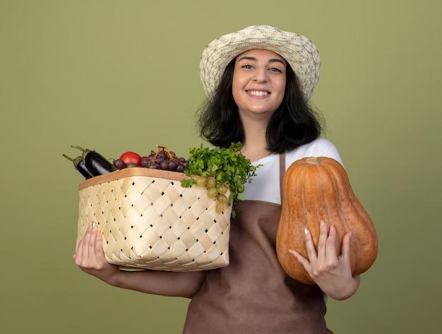 Jovem morena sorridente jardineira de uniforme, usando chapéu de jardinagem, segurando uma cesta de vegetais e abóbora isolada na parede verde oliva
