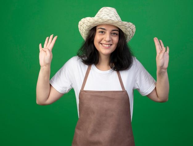 Jovem morena sorridente, jardineira feminina de óculos óticos e uniforme, usando chapéu de jardinagem, gesticula oito com dedos isolados na parede verde