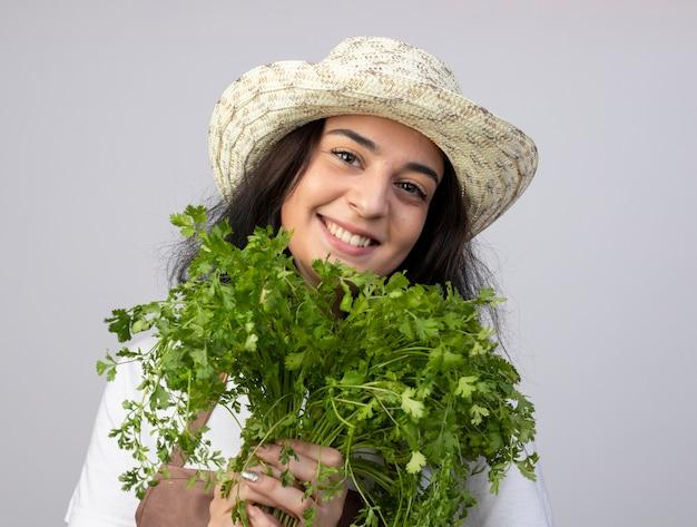 Jovem morena sorridente jardineira feminina de uniforme, usando chapéu de jardinagem, segurando coentro isolado na parede branca com espaço de cópia