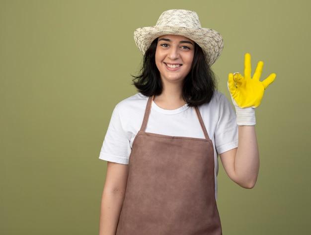 Jovem morena sorridente jardineira feminina de uniforme, usando luvas e chapéu de jardinagem, gestos sinal de mão ok isolado na parede verde oliva