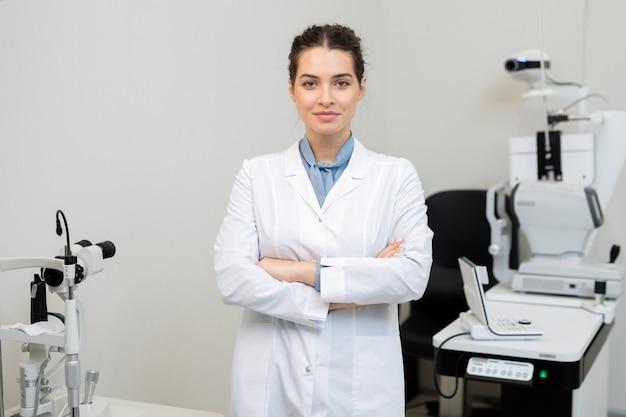 Jovem, morena, sorridente, mulher, oftalmologista, de jaleco, cruzando os braços sobre o peito, em pé contra equipamentos médicos em clínicas