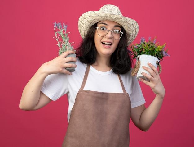 Jovem morena surpresa com óculos e uniforme, usando um chapéu de jardinagem e segurando vasos de flores isolados na parede rosa com espaço de cópia