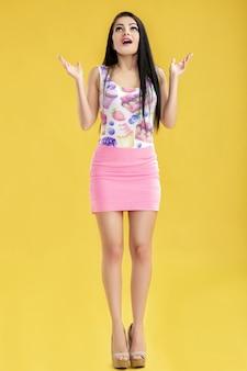 Jovem morena surpresa de saia rosa e blusa amarela