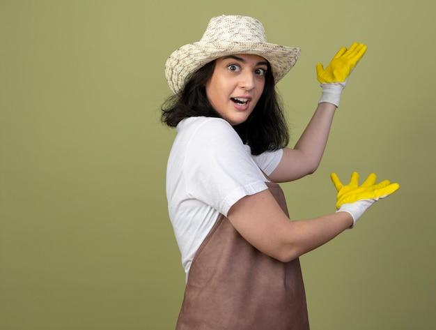 Jovem morena surpresa jardineira feminina de uniforme, usando chapéu de jardinagem e luvas apontando para trás com as mãos isoladas na parede verde oliva
