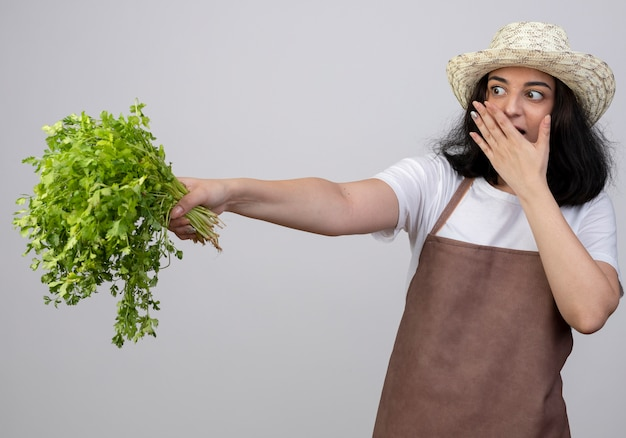 Jovem morena surpresa, jovem jardineira, de uniforme, usando chapéu de jardinagem, coloca a mão na boca e segura coentro isolado na parede branca