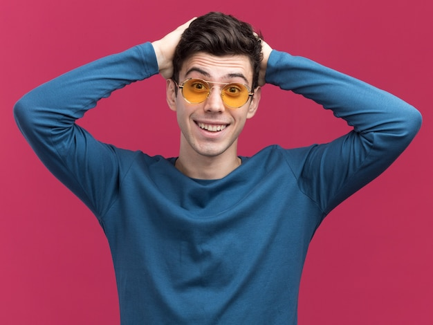 Jovem morena surpreso, caucasiano, usando óculos de sol, coloca as mãos na cabeça isolada na parede rosa com espaço de cópia