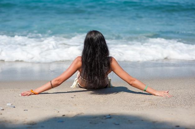 Jovem morena toma banho de sol na praia, as ondas atingem as pernas