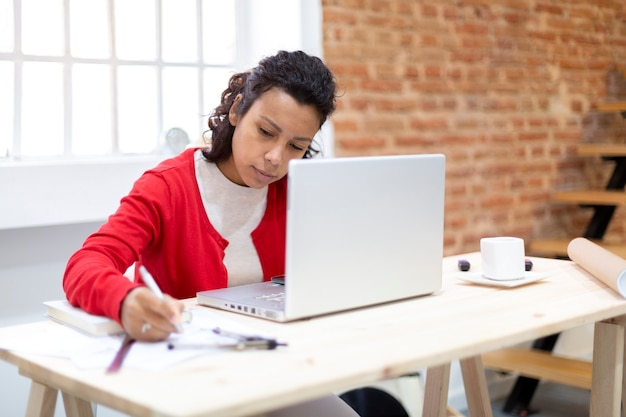 Jovem morena trabalhando duro em seu escritório em casa. espaço para texto. conceito de planos e novos projetos.