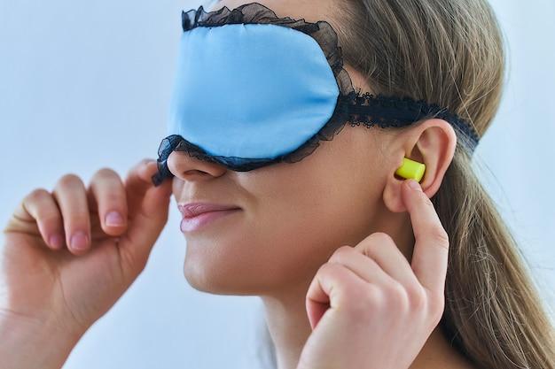 Jovem morena usando tampões para os ouvidos e máscara para melhor sono e bons sonhos