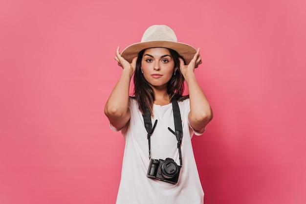 Jovem morena vestida de camiseta leve com uma câmera pendurada no pescoço, coloca um chapéu de palha na cabeça com pensamentos sobre a futura jornada