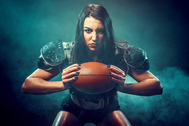 Jovem morena vestindo uniforme de jogador de futebol de rugby, posando com bola.