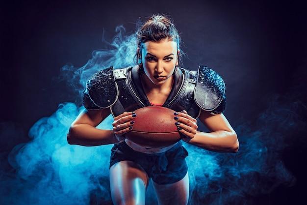 Jovem morena vestindo uniforme sexy de jogador de futebol de rugby posando com bola.
