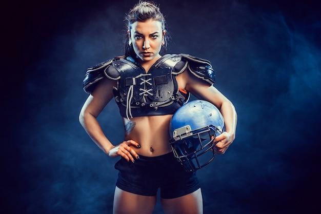 Jovem morena vestindo uniforme sexy de jogador de futebol de rugby posando.