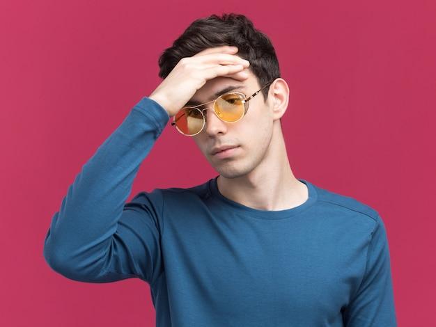 Jovem moreno caucasiano decepcionado com óculos de sol coloca a mão na testa isolada na parede rosa com espaço de cópia