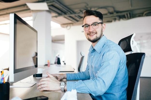 Jovem moreno de óculos está trabalhando com um computador em sua área de trabalho no escritório. ele veste camisa azul e sorri para a câmera. vista lateral.