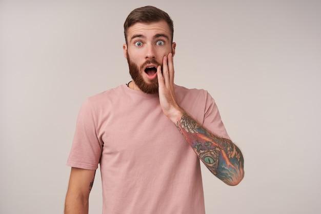 Jovem moreno tatuado e barbado espantado com corte de cabelo curto, mantendo a palma da mão na bochecha e abrindo a boca com surpresa, olhos arredondados e sobrancelhas levantadas enquanto posava em branco