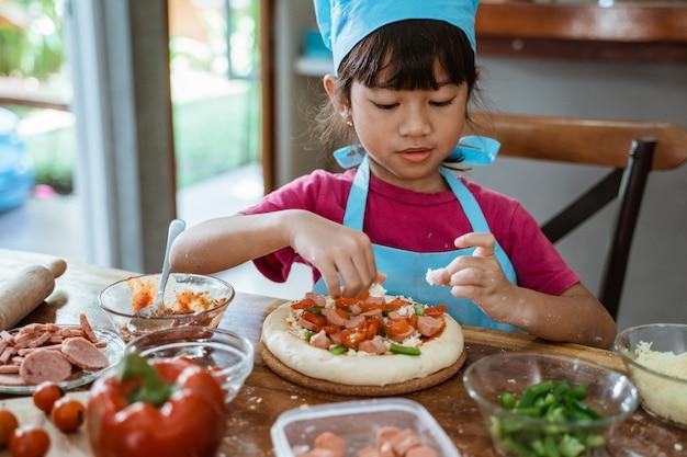 Jovem mostra uma pizza na mesa da cozinha