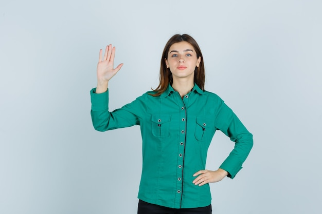 Jovem, mostrando a palma da mão na camisa verde e olhando confiante, vista frontal.
