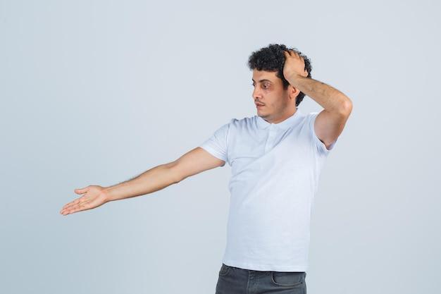 Jovem mostrando algo abaixo em camiseta branca, calça e parecendo confuso. vista frontal.