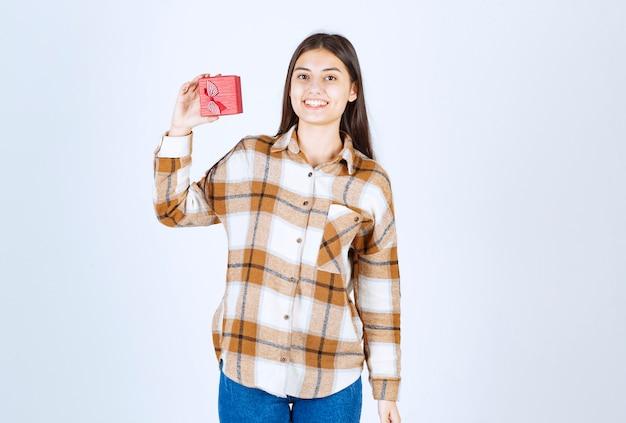 Jovem mostrando caixa de presente vermelha na parede branca.