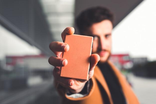 Jovem mostrando carteira focada e pessoa desfocada na rua