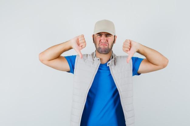 Jovem mostrando dois polegares para baixo em camiseta, jaqueta, boné e parecendo triste. vista frontal.