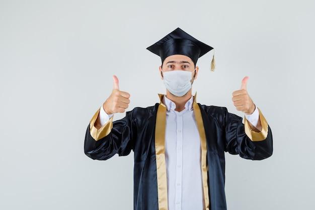 Jovem mostrando dois polegares para cima em uniforme de pós-graduação e parecendo confiante, vista frontal.