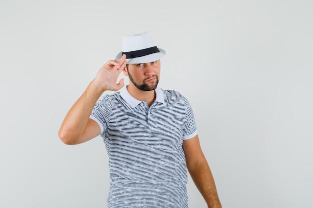 Jovem mostrando gesto de adeus em t-shirt, chapéu e olhando sério, vista frontal.