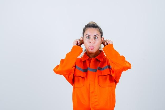 Jovem, mostrando gesto de macaco em uniforme de trabalhador e olhando estranha, vista frontal.